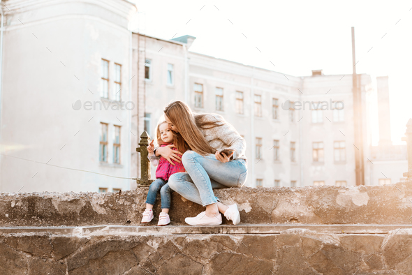 Mom and daughter sit together on the fence - Stock Photo - Images