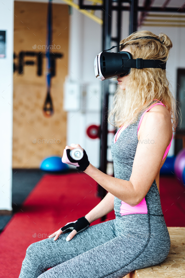 Beautiful girl in the gym with VR headset - Stock Photo - Images