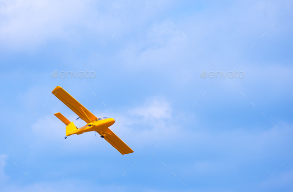 Yellow bright flying airplane in the blue sky - Stock Photo - Images