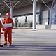 Two Construction Workers in Orange Uniform and Helmets Meeting Each Other at the Bulding Object - VideoHive Item for Sale