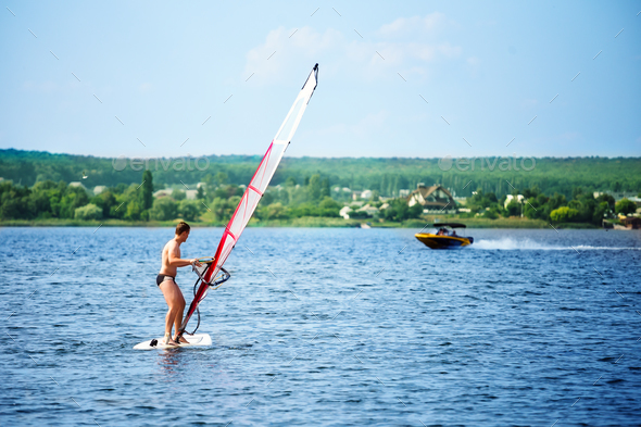 Windsurfer on board with a white sail floating away - Stock Photo - Images