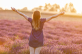 Happy young woman on lavender field at sunset - PhotoDune Item for Sale