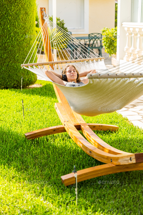 Girl relaxing and listening to music in hammock - Stock Photo - Images