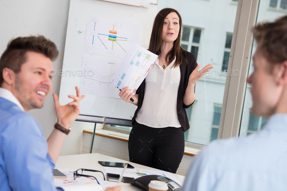 Female Professional Giving Presentation To Male Colleagues - Stock Photo - Images