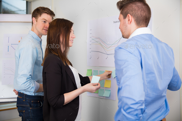 Businesswoman Sticking Adhesive Notes While Standing By Colleagu - Stock Photo - Images
