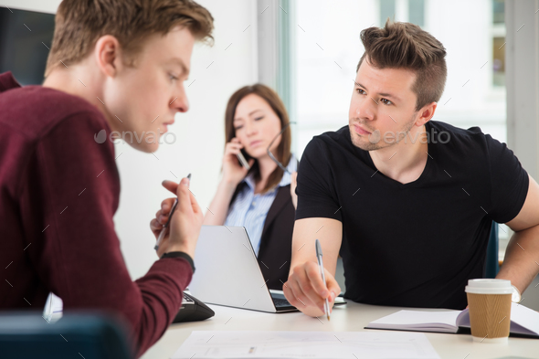Professionals Planning While Colleague Using Mobile Phone In Off - Stock Photo - Images