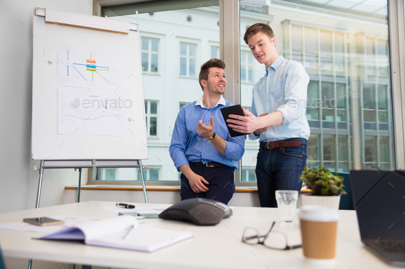 Businessmen Communicating Over Digital Tablet Against Window - Stock Photo - Images
