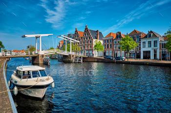 Spaarne river with boat and Gravestenenbrug bridge in Haarlem, N