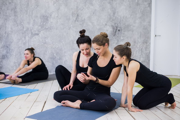 Cute girl sitting and socializing with the group after their yoga class - Stock Photo - Images