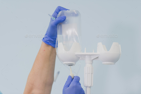 Doctor's hand and infusion drip in hospital on blurred background - Stock Photo - Images