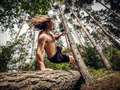Young man jumping over a tree trunk in the forest. - PhotoDune Item for Sale
