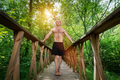 Young man standing on a footbridge in the forest. - PhotoDune Item for Sale