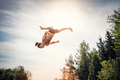 Young man jumping high in the sky. - PhotoDune Item for Sale