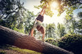Young man doing a handstand on a tree trunk in the forest. - PhotoDune Item for Sale