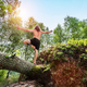 Young man standing on a tree trunk in the forest. - PhotoDune Item for Sale