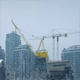 Large Cranes In City With Snow Falling