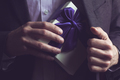 Man in suit opening a gift with purple ribbon
