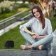 brunette female sitting in contemporary green park - PhotoDune Item for Sale