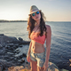 stylish brunette woman on background of sunset, sea rocky coast - PhotoDune Item for Sale