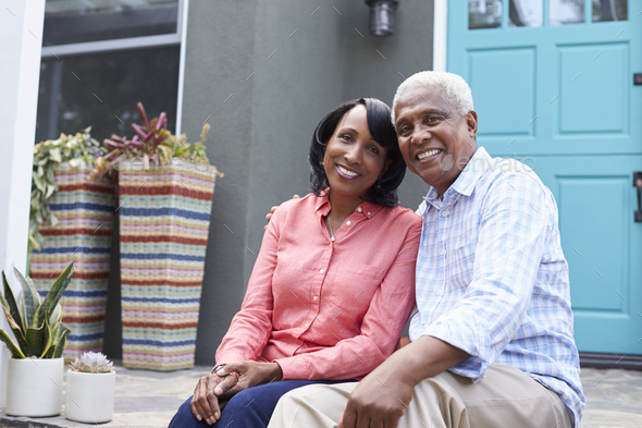 Senior couple sit on steps outside their house, close up - Stock Photo - Images