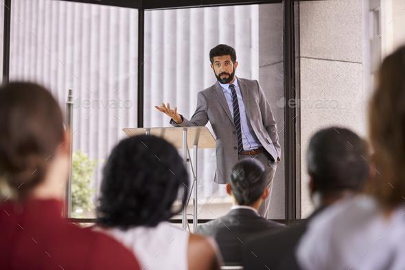 Hispanic man presenting business seminar leaning on lectern - Stock Photo - Images