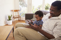 Grandfather And Grandson At Home Using Digital Tablet - PhotoDune Item for Sale