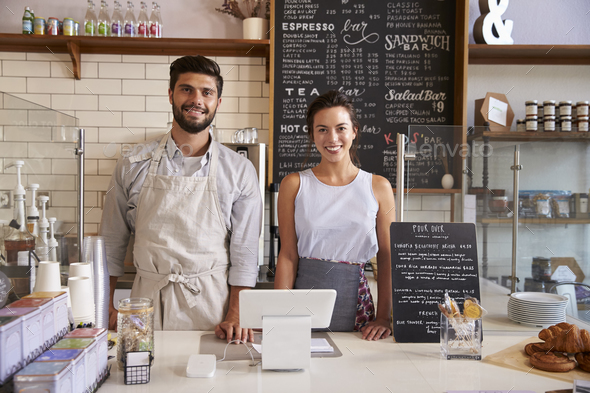 Couple ready to serve behind the counter of a coffee shop - Stock Photo - Images
