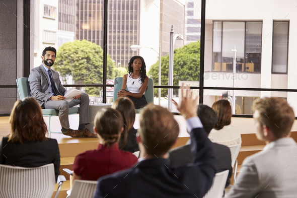 Male and female seminar speakers take question from audience - Stock Photo - Images