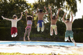 Rear View Of Children Jumping Into Outdoor Swimming Pool
