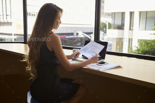 Businesswoman sitting in modern office reading a document - Stock Photo - Images