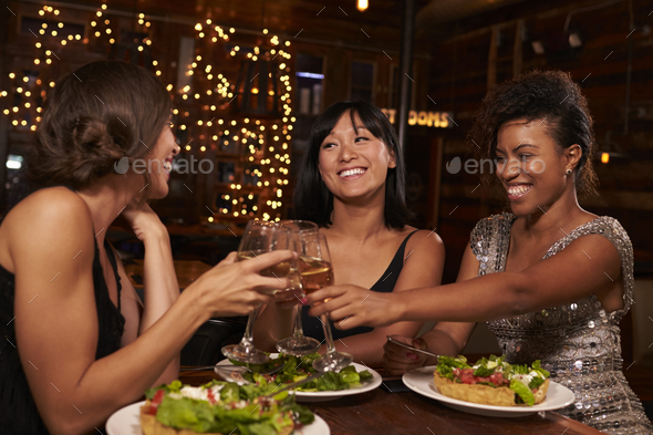 Three female friends make a toast over dinner at restaurant - Stock Photo - Images