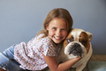 Portrait Of Smiling Girl With Pet British Bulldog