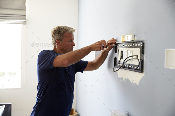 Man Fitting Bracket For Flat Screen TV Onto Wall - Stock Photo - Images