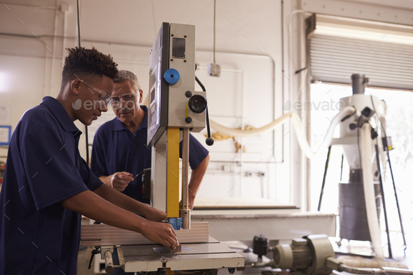 Carpenter Training Male Apprentice To Use Mechanized Saw - Stock Photo - Images