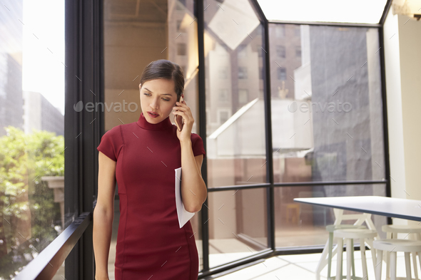 Young young white businesswoman using phone in modern office - Stock Photo - Images
