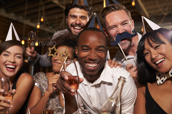 Friends in party hats celebrating New Year at bar, close up - Stock Photo - Images