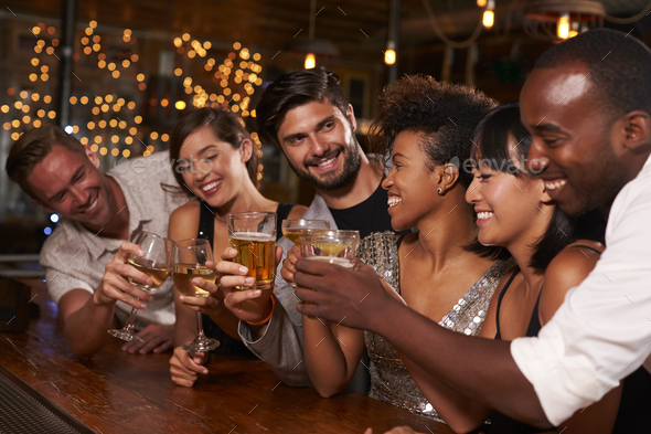 Young adult friends making a toast by the bar at a party - Stock Photo - Images