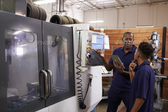 Engineer Training Young Male Apprentice On CNC Machine - Stock Photo - Images
