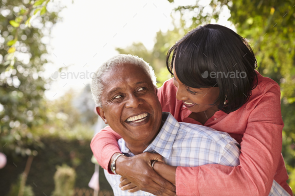 Senior black couple piggyback, looking at each other - Stock Photo - Images