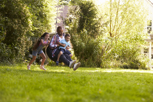 Daughter Pushing Father And Son On Tire Swing In Garden - Stock Photo - Images
