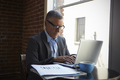 Mature Businessman Working On Laptop By Office Window - PhotoDune Item for Sale