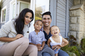 Portrait Of Family Sitting On Steps Outside Home - PhotoDune Item for Sale