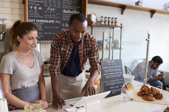 Barista at coffee shop showing till to new employee, close up - Stock Photo - Images