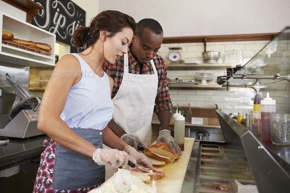 Couple preparing sandwiches at a sandwich bar counter - Stock Photo - Images