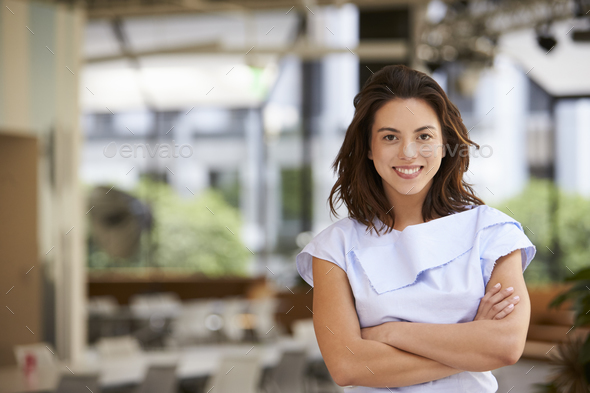 Portrait of young mixed race businesswoman with arms crossed - Stock Photo - Images