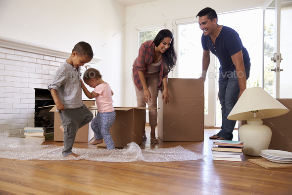 Family Unpacking Boxes In New Home On Moving Day - Stock Photo - Images