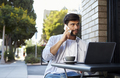 Bearded young man with laptop on the phone outside a cafe