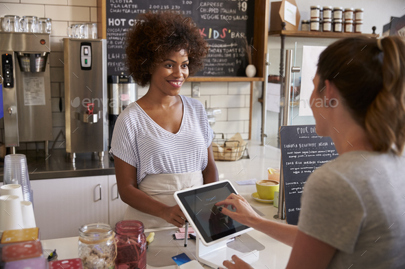 Customer at counter of coffee shop pays using touch screen - Stock Photo - Images