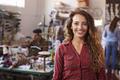 Long haired white female clothes designer in design studio