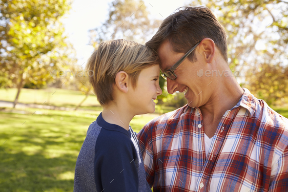 Father and young son in a park, heads together, side view